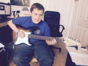 child playing fender electric guitar